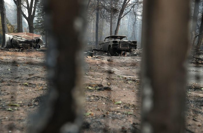A burned out car sits next to a home destroyed by the Camp Fire on November 16, 2018 in Paradise, California. Reuters