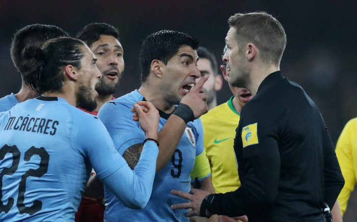 CONTENTIOUS: Uruguay's Luis Suarez argues with referee Craig Pawson after he awarded a penalty to Brazil. While the referee adjudged Danilo to have been brought down by Diego Laxalt, Uruguay claimed there was a handball from the Brazilian in the build-up