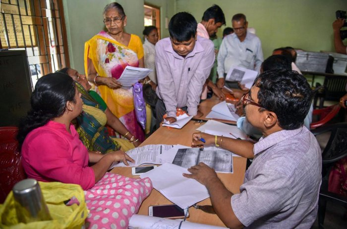 People verify the National Register of Citizens (NRC) forms to file claims and objections at an NRC centre, in Guwahati. PTI file photo