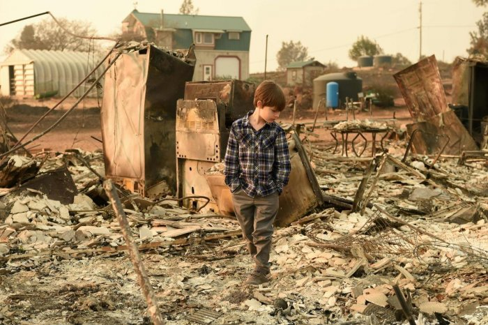 Jeremie Saylors, 11, walks through the burned remains of his home in Paradise, California on November 18, 2018. - The family lost a home in the same spot to a fire 10 years prior. (Photo by Josh Edelson / AFP)