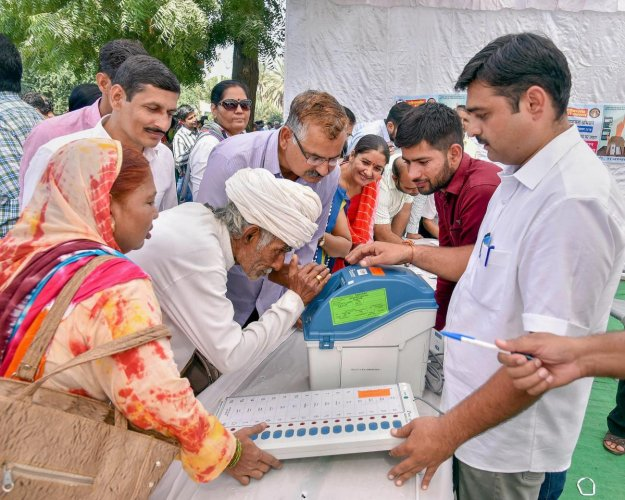 Electoral officials demonstrate how to use an Electronic Voting Machine (EVM) and Voter-Verified Paper Audit Trail (VVPAT) to locals during a voter awareness programme ahead of Rajasthan State Assembly elections, in Bikaner. (PTI Photo)