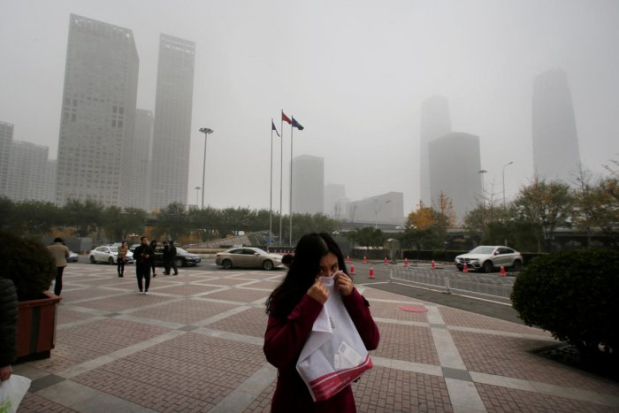 A woman covers her nose as she walks in the central business district on a polluted day after a yellow alert was issued for smog, in Beijing, China. (REUTERS File Photo)