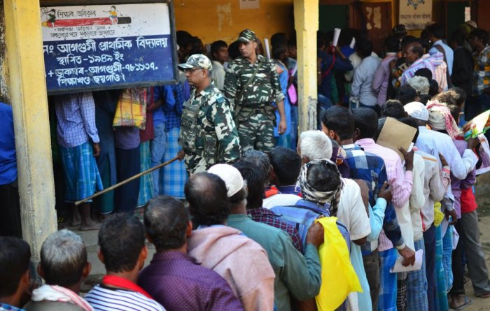 People stand in line to check their names on the first draft of the National Register of Citizens (NRC) at Gumi village of Kamrup district in the Indian state of Assam on January 1, 2018. Around 13 million people in northeastern India's Assam woke up to u