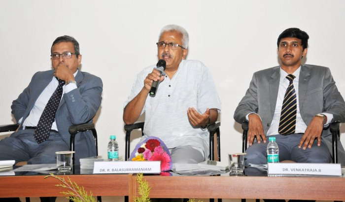 R Balasubramaniam, founder and chairman of GRAAM, at an international conference on 'Economic Growth and Sustainable Development: Emerging Trends' in Mysuru on Friday. SDM IMD director N R Parashuraman and professor B Venkataraja look on.