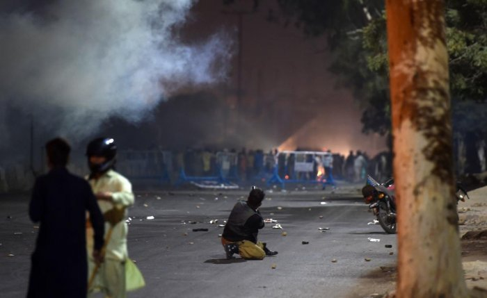 A Pakistani policeman fires teargas towards protesters during clashes after the arrest of hardline cleric Khadim Hussain Rizvi in Karachi on November 24, 2018. AFP