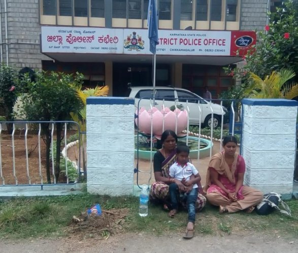 Constable Shivanna's wife, child and a family member stage a protest in front of the SP's office in Chikkamagaluru.