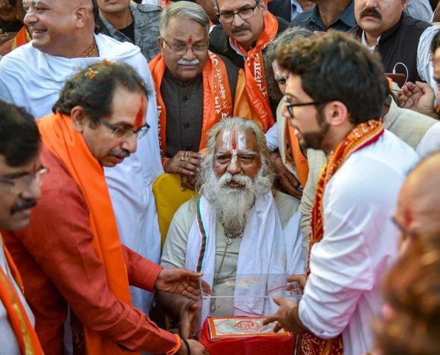 Shiv Sena chief Uddhav Thackeray and Yuva Sena chief Aditya Thackeray present a silver brick to Ram Janmabhoomi Nyas chief, Mahant Nritya Gopal Das, at Laxman Qila ahead of the Ram Temple event to be held tomorrow, in Ayodhya, Saturday, Nov.24, 2018. (PTI