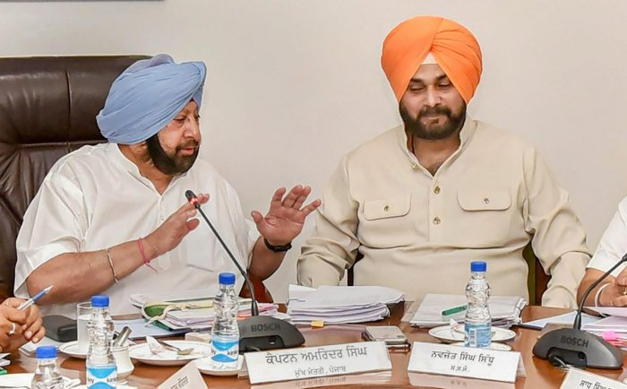 Punjab Chief Minister Captain Amarinder Singh with his colleague Navjot Singh Sidhu during a Cabinet meeting in Chandigarh on Tuesday. PTI