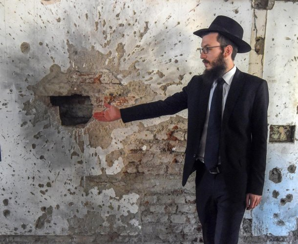 TRACES OF TERROR: Rabbi Israel Kozlovsky gestures at the bullet marks in Nariman House from the 26/11 attacks, in Mumbai on Sunday. PTI