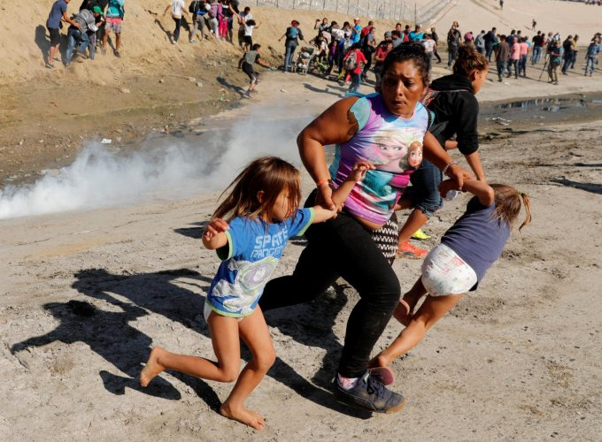 A migrant family from Honduras, part of a caravan of thousands travelling from Central America en route to the United States, runs from tear gas released by US border patrol near the fence between Mexico and the United States in Tijuana, Mexico, on Novemb