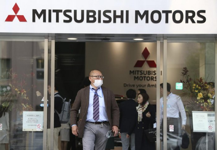 People visit a showroom at the headquarters of Mitsubishi Motors Corp in Tokyo, Monday, Nov. 26, 2018. The board of Mitsubishi Motors is meeting Monday to decide whether to oust Carlos Ghosn as chairman at the Japanese automaker, which is allied with Rena