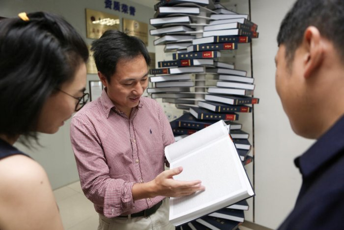 "Scientist He Jiankui shows ""The Human Genome"", a book he edited, at his company Direct Genomics in Shenzhen, Guangdong province, China August 4, 2016. Picture taken August 4, 2016. REUTERS/Stringer ATTENTION EDITORS - THIS IMAGE WAS PROVIDED BY A THIRD PA"