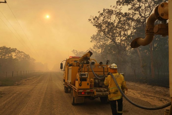 Firefighters refill their water from a water tanker in Pacific Drive in Deepwater National Park area of Queensland on November 28, 2018. AFP