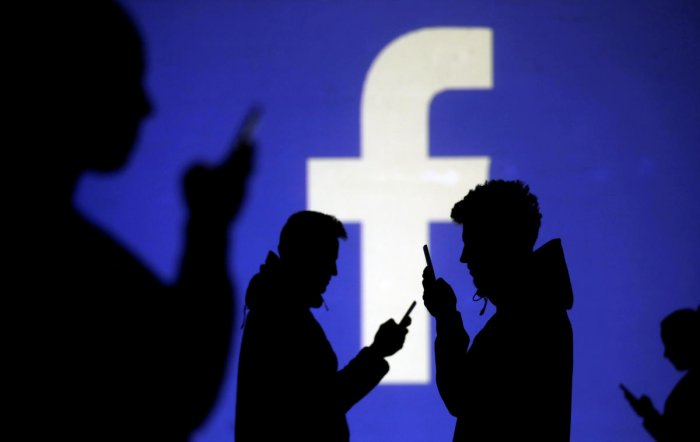 Silhouettes of mobile users are seen next to a screen projection of the Facebook logo in this picture illustration. Reuters file photo