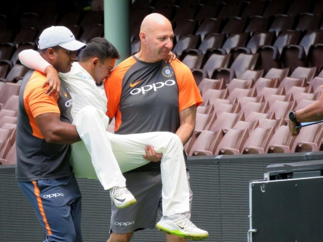 India's batsman Prithvi Shaw (C) is carried off after injuring his ankle whilst fielding on the third day of the tour match against Cricket Australia XI at the SCG in Sydney. AFP Photo