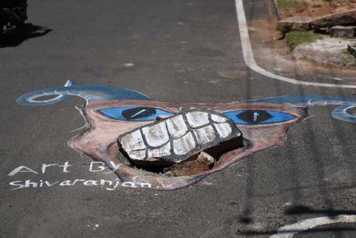 Halaguru Shivaranjan, who is pursuing his bachelors in Visual Arts at Charmarajendra Academy Of Visual Arts (CAVA), has been drawing the attention of authorities through his paintings that highlight the potholes and uncovered manholes. (DH Photo)