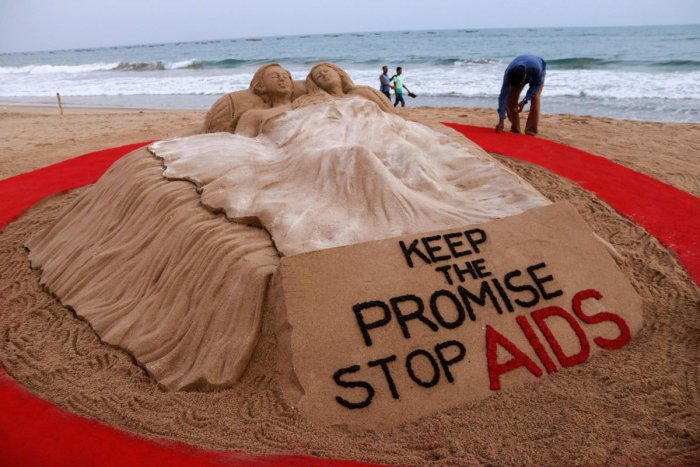 Sand sculptor Sudarsan Pattnaik creates a sand art to spread awareness and extend solidarity towards people living with AIDS, on the eve of World AIDS Day in Puri. PTI photo