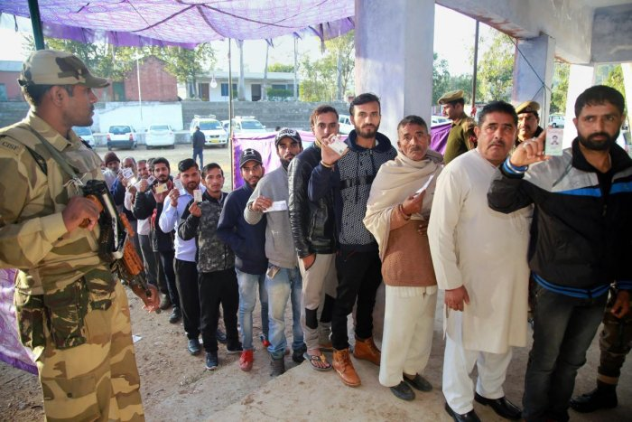 Voters stand in a queue at a polling station during the 2nd phase of the panchayat elections at Tikri village, in Udhampur district, on Tuesday. PTI