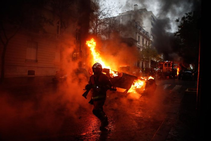 Firemen are at work to extinguish a burning car on the sideline of a demonstration by Yellow vests (Gilets jaunes) protesters against rising oil prices and living costs, on December 1, 2018 in Paris. (Photo by Abdulmonam EASSA / AFP)