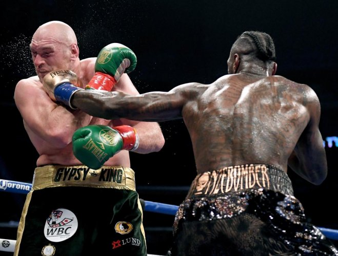 Deontay Wilder lands a punch on Tyson Fury during their WBC Heavyweight title bout in Los Angeles on Saturday. AFP