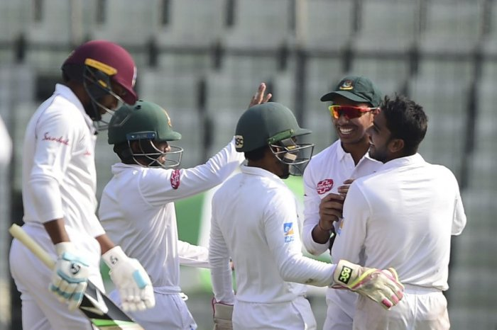 Mehidy Hasan (right) celebrates with team-mates after the dismissal of Devendra Bishoo in Dhaka onSunday. AFP