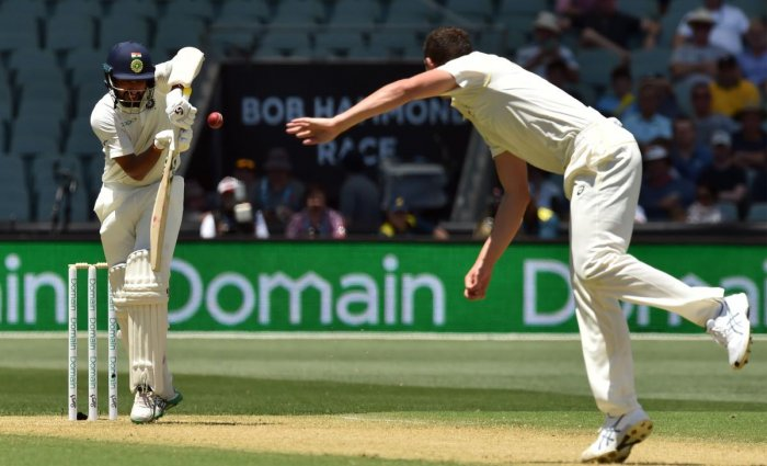 India's batsman Cheteshwar Pujara (L) plays a shot off Australia's paceman Josh Hazlewood (R) during day one of the first cricket Test match at the Adelaide Oval on December 6, 2018. (Photo by PETER PARKS / AFP)