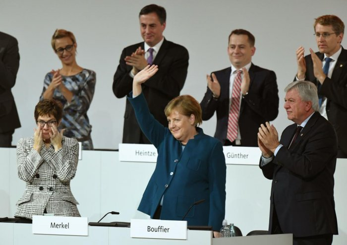 German Chancellor and leader of the CDU Angela Merkel greets the audience as she is applauded by CDU Secretary General and Hesse's State Premier and CDU Deputy Chairman Volker Bouffier during a CDU congress on December 7, 2018 at a fair hall in Hamburg, northern Germany. AFP