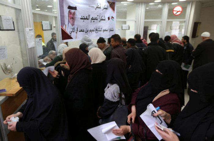 Palestinian Hamas-hired civil servants wait to receive their salaries paid by Qatar as a banner showing a picture of Qatar's Sheikh Tamim bin Hamad Al Thani is seen, in Khan Younis in the southern Gaza Strip. Reuters