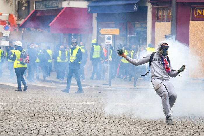 "Protestors clash with police forces on December 8, 2018 in Paris, during a protest of ""yellow vests"" (gilets jaunes) against rising costs of living they blame on high taxes. - Paris was on high alert on December 8 with major security measures in place ahe"
