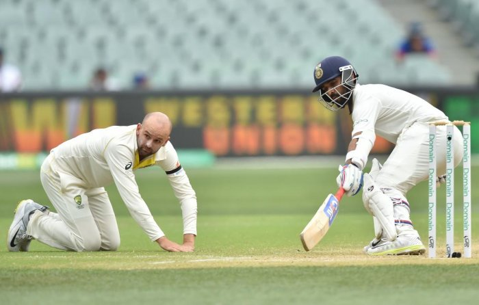 Ajinkya Rahane (R) runs between the wickets as Australia's Nathan Lyon (L) looks on during day four of the first Test cricket match at the Adelaide Oval on December 9, 2018. (AFP Photo)