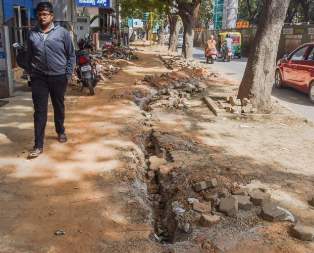 Pedestrian walks along  an under construction footpath in Jayanagar, Bengaluru. DH photo by  S K Dinesh.