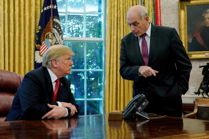 FILE PHOTO: U.S. President Donald Trump speaks to White House Chief of Staff John Kelly after an event with reporters in the Oval Office at the White House in Washington, U.S. October 10, 2018. REUTERS/Jonathan Ernst/File Photo
