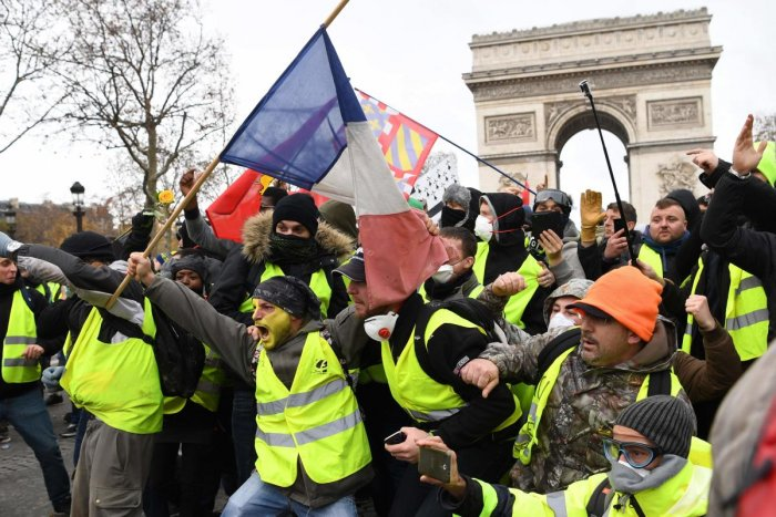 "Protestors wearing ""yellow vest"" (gilet jaune) gesture on December 8, 2018 near the Arc de Triomphe in Paris during a protest against rising costs of living they blame on high taxes. AFP Photo"
