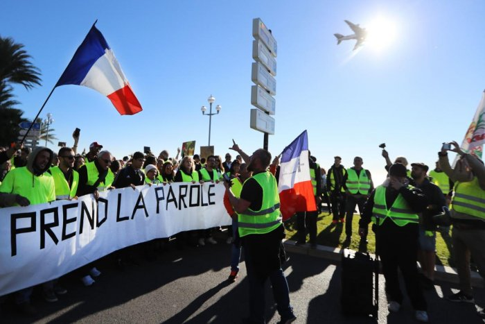 "Protestors hold a banner reading ""The People speaks out"" on the ""Promenade des Anglais"" during a protest of Yellow vests (Gilets jaunes) against rising oil prices and living costs, in Nice, southeastern France. AFP file photo."