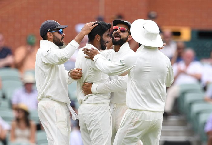 India's captain Virat Kohli (2nd R) celebrates with his teammate Jasprit Bumrah (2nd L) after Bumrah dismissed Australian batsman Peter Handscomb for 34 runs on day two of the first test match between Australia and India at the Adelaide Oval in Adelaide,
