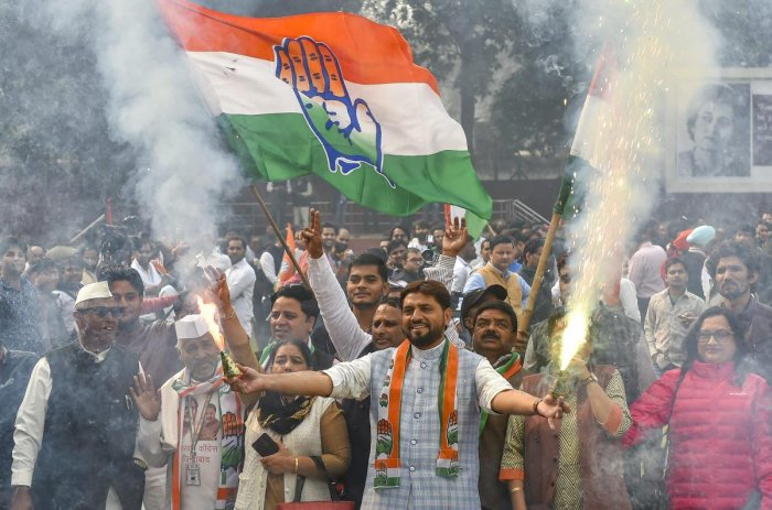 Congress party workers burst firecrackers as they celebrate the counting trends for the recent Assembly elections, at AICC headquarters in New Delhi. PTI