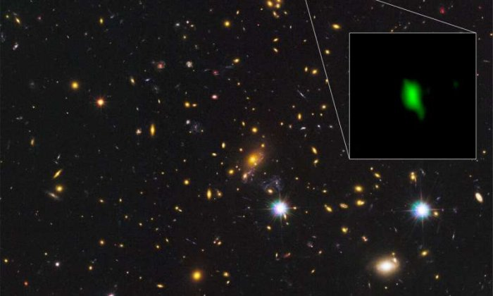 The galaxy cluster MACS J1149.5+2223 taken with the NASA/ESA Hubble Space Telescope and the inset image is the galaxy MACS1149-JD1 located 13.28 billion light-years away observed with ALMA. Here, the oxygen distribution detected with ALMA is depicted in green. Credit: ALMA (ESO/NAOJ/NRAO), NASA/ESA Hubble Space Telescope, W. Zheng (JHU), M. Postman (STScI), the CLASH Team, Hashimoto et al.