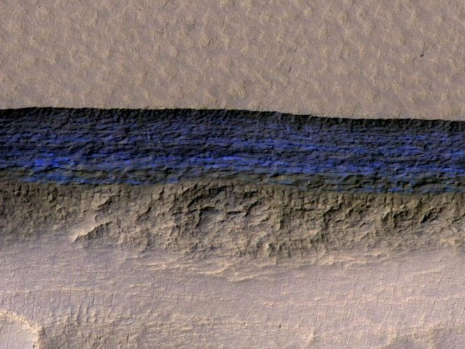 A cross-section of underground ice is exposed at the steep slope that appears bright blue in this enhanced-color view from the HiRISE camera on NASA's Mars Reconnaissance Orbiter. The scene is about 550 yards wide. The scarp drops about 140 yards from the level ground in the upper third of the image. Credits: NASA/JPL-Caltech/UA/USGS