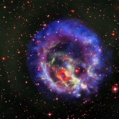The new composite image of neutron star E0102, released on May 23, combines data from NASA's Chandra X-Ray Observatory (seen in blue and purple), the Multi Unit Spectroscopic Explorer instrument on the European Southern Observatory's Very Large Telescope