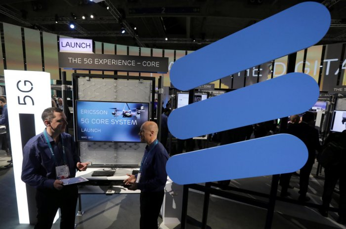 FILE PHOTO: Ericsson's employees stand inside their booth at Mobile World Congress in Barcelona, Spain. REUTERS