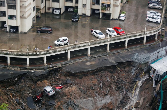 Cars are seen amidst debris after the wall of a residential building collapsed due to heavy rains in Mumbai. REUTERS