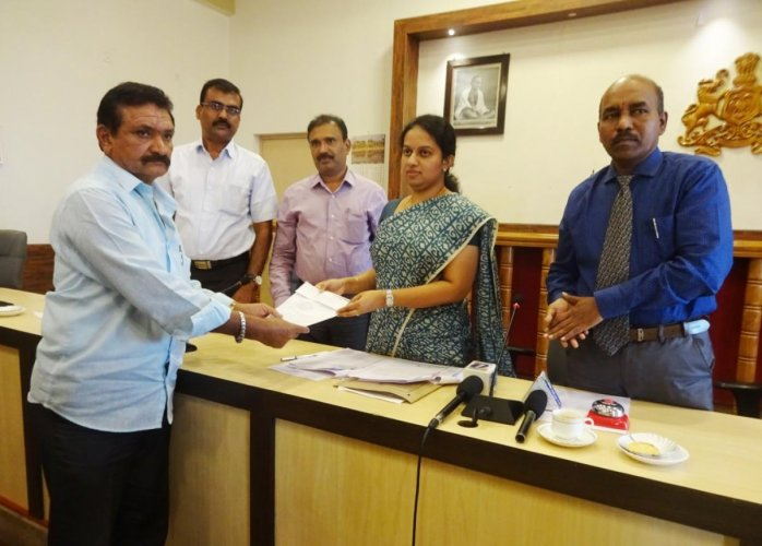 Deputy Commissioner P I Sreevidya symbolically hands over a token to a farmer on Thursday.