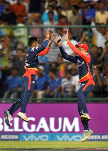 Delhi Daredevils bowler Sandeep Lamichhane (left) celebrates the wicket of Mumbai Indians batsman K Pollard during an IPL match, in New Delhi on Sunday.