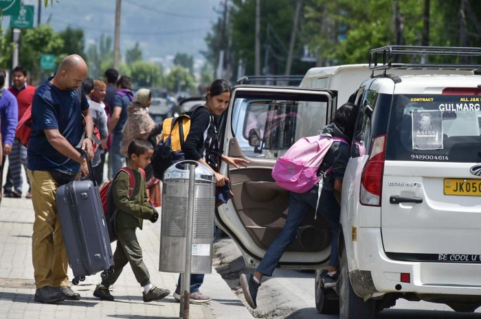 A tourist family boards a taxi at Boulevard Road in Srinagar on Tuesday. Tourism department and stakeholders have expressed apprehensions that the death of a tourist from Tamil Nadu in recent clashes, could negatively impact the arrival of visitors to Kas