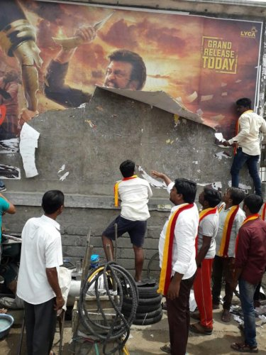 Kannada activists tear up a poster of 'Kaala' film at Sangameshwar theatre in Sindhanur, Raichur district on Thursday. dh photo