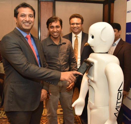Puravankara Limited COO Anand Narayanan interacts with the robot. DH Photo