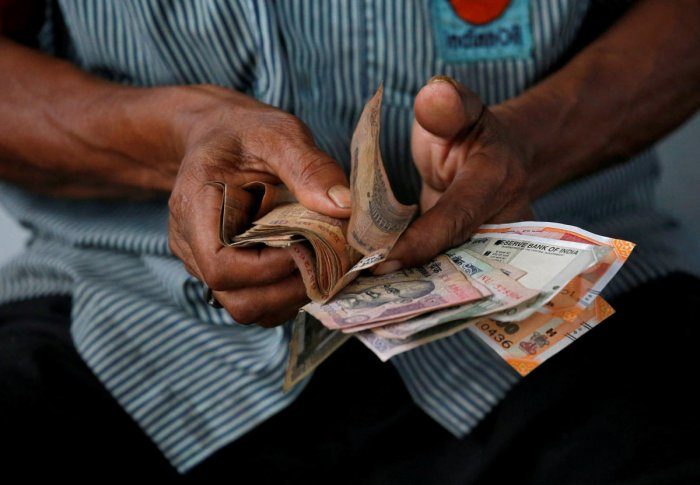 An attendant at a fuel station arranges Indian rupee notes in Kolkata. REUTERS