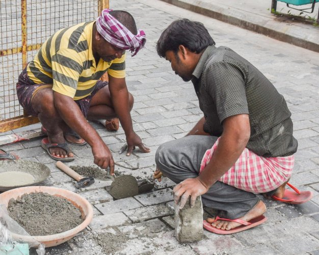 Workers repair a loosened cobblestone on Church Street, Bengaluru, on Friday. DH PHOTO/S K Dinesh