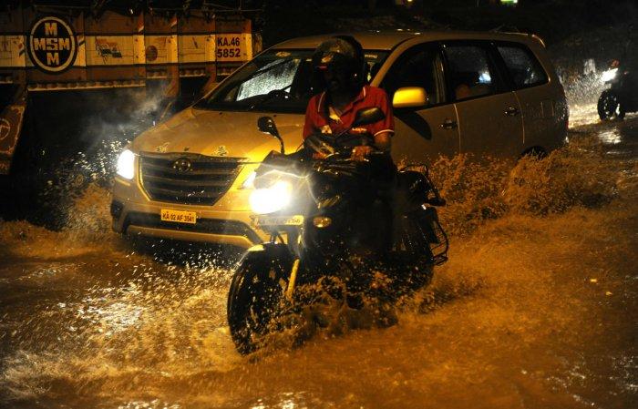 Motorists struggle to navigate the waterlogged Mysuru Road at Nayandanahalli junction on Wednesday night. DH PHOTO/Srikanta Sharma R