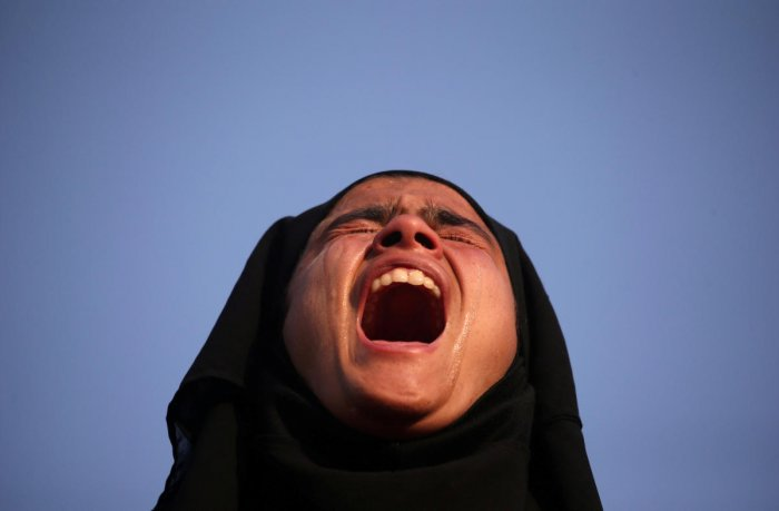 A girl cries as she watches the body of Mehraj-ud-Din Bangroo, a suspected militant, who according to local media was killed in a gunbattle with security forces, during his funeral procession in Srinagar on October 17, 2018. (REUTERS)